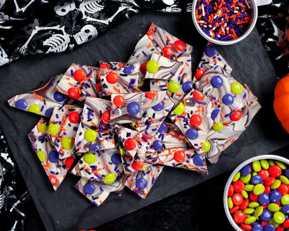 Top down view of a serving tray covered with Halloween Chocolate Bark. It is surrounded by Halloween m&ms, sprinkles, mini pumpkins, and a skeleton linen.