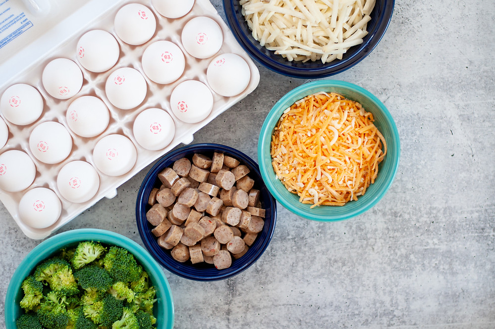 Ingredient shot for this breakfast casserole recipe, including eggs, hash browns, cheese, chicken sausage, and broccoli
