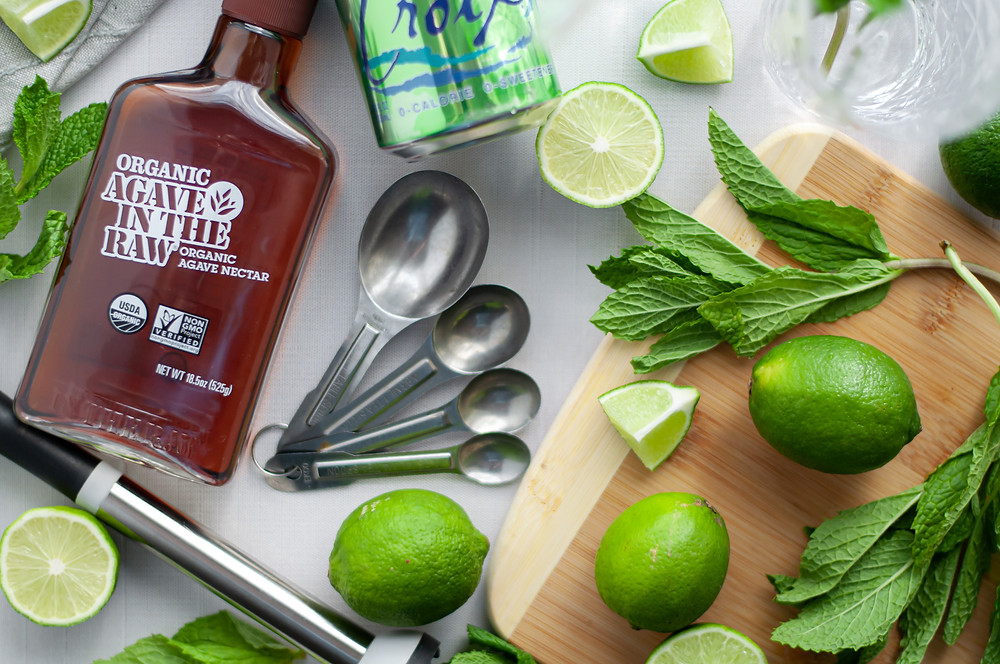 Artistic ingredient shot for this virgin mojito recipe. Top down view of mint, limes (full sized, wedges, and slices), agave, sparking water, measuring spoons, and a muddler.