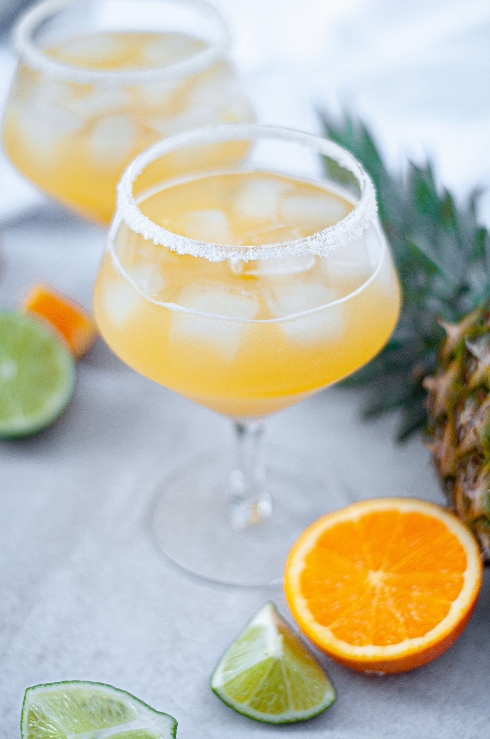 Two glasses with salted rims filled with this skinny pineapple margarita recipe and ice. Surrounded by a pineapple, orange slices, and lime slices.