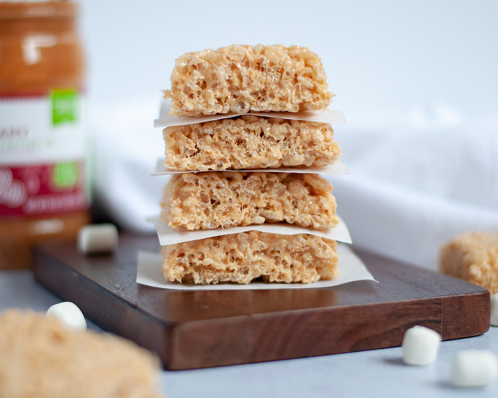 stack of 4 peanut butter rice crispy treats. Surrounded by other rice krispie squares, mini marshmallows, and a jar of peanut butter in the background.