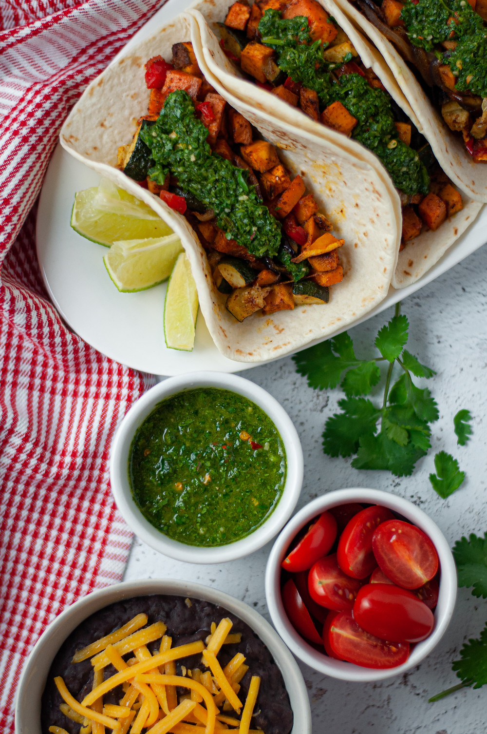 Top down view of three vegetable tacos served with a side of lime wedges, chimichurri sauce, tomatoes, and a side of refried beans