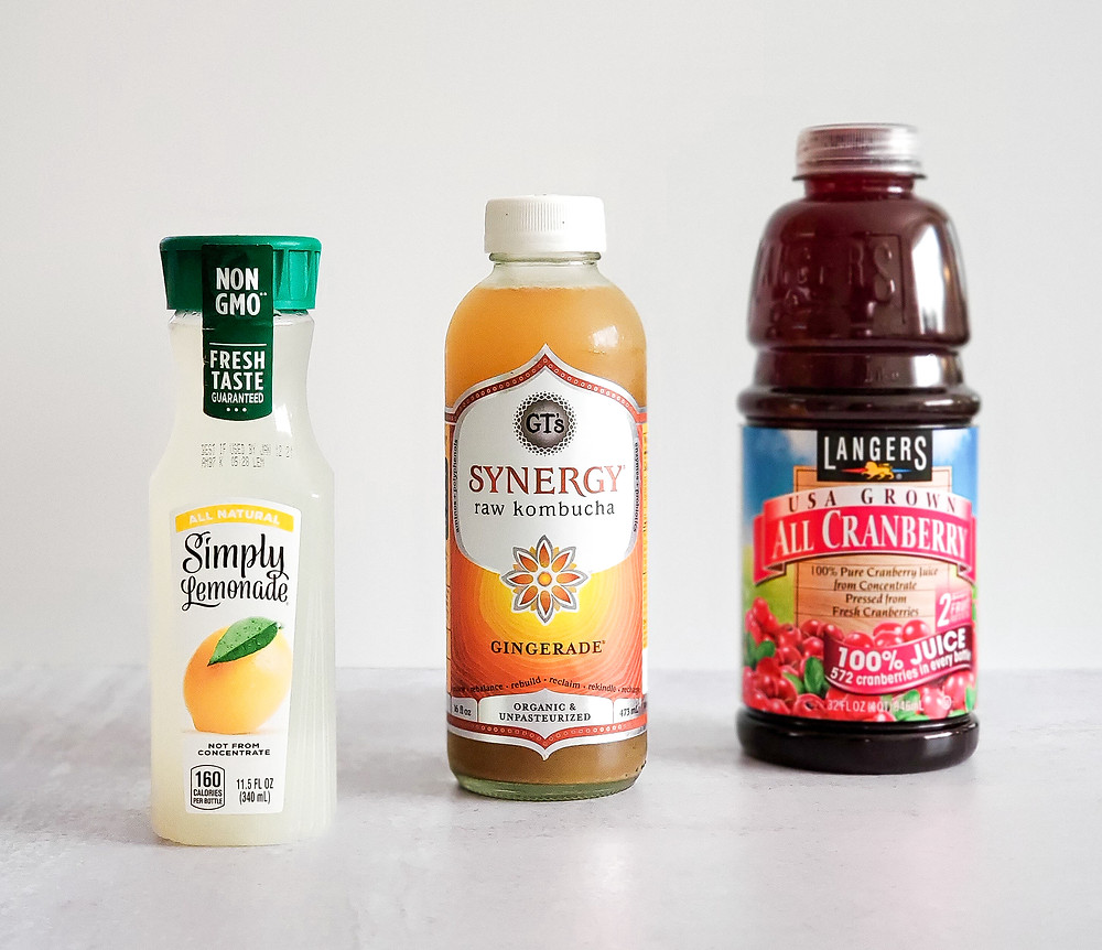 Ingredient shot for this mocktail recipe, showing lemonade, ginger kombucha, and 100% cranberry juice