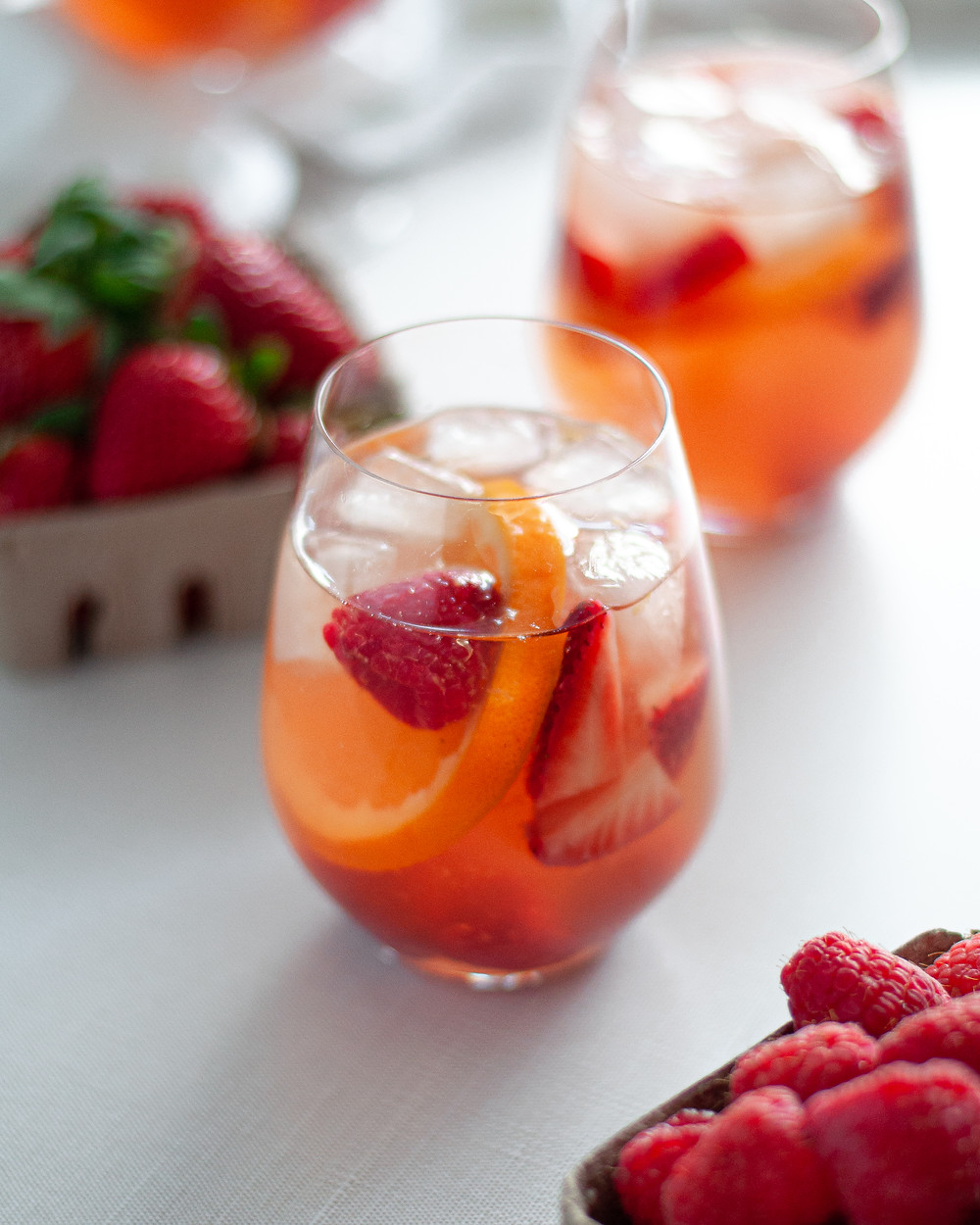 Close up of a stemless wine glass filled with rosé sangria, ice, berries, and orange slices. There is also a container of raspberries in the foreground, a container of strawberries in the background, and additional glasses of rosé sangria in the background.