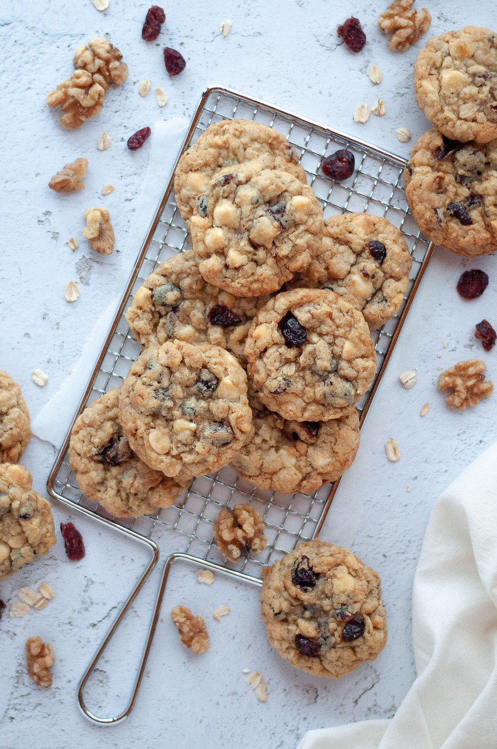 Top down view of a pile of these cranberry oatmeal cookies surrounded by more cookies and walnuts, oats, and craisins