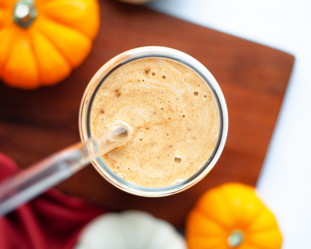 Top down view of a healthy pumpkin protein shake. The pumpkin smoothie is sitting on a wood cutting board and is surrounded by pumpkins.