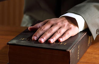 A witness's hand on the Bible.