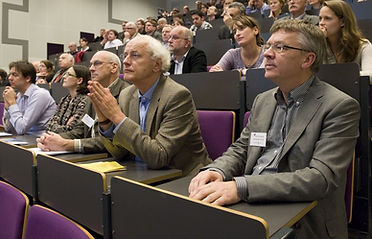 Image of conferees listening to a presenter.