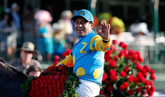 Smiling jockey holds blanket of roses after winning horse race.