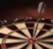 """Photo of a  dart board with a dart in the """"bullseye"""" position."""