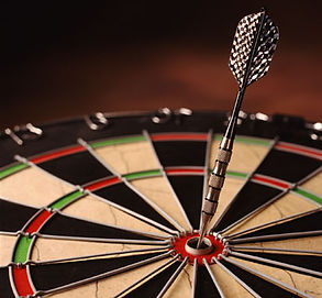 "Photo of a  dart board with a dart in the ""bullseye"" position."