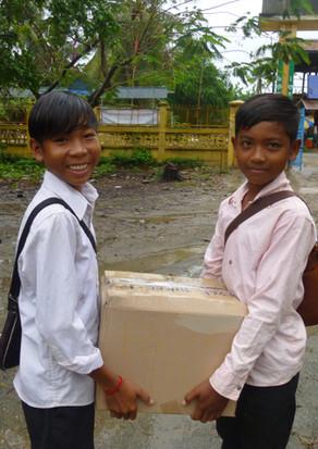 寄付された教科書を図書館に運ぶバティ高校の生徒