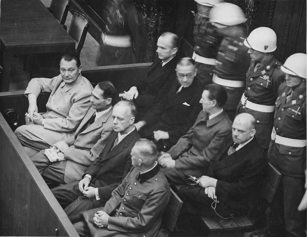 紐倫堡審判中(從左向右)的戈林、赫斯、里賓特洛甫、凱特爾,後排:鄧尼茨、雷德爾、席拉赫、紹克爾