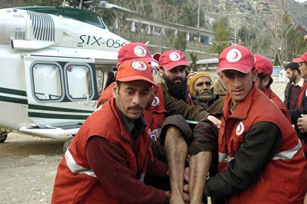 巴基斯坦志願者將受傷的倖存者轉移到一架直升機上。(SAJJAD QAYYUM/AFP/Getty Images)
