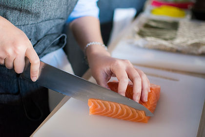 person-slicing-meat-on-white-chopping-bo