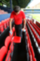 Man cleaning the seats at a football ground