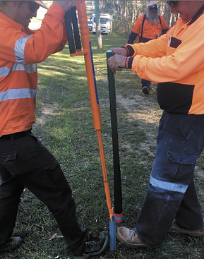 2 men inserting the pole in to the ground