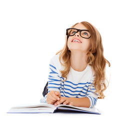 education and school concept - smiling little student girl with book and eyeglasses lying on the flo