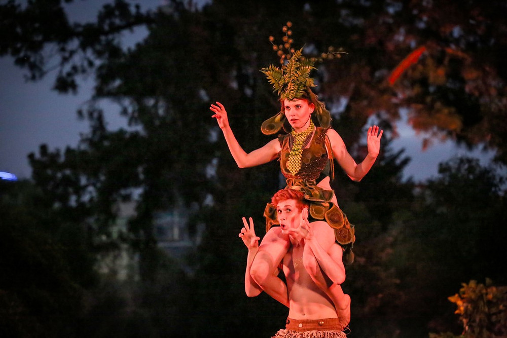 A woman sits on the shoulders of a man while in costume for the play A Midsummer Night's Dream.