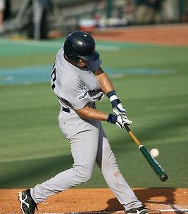 A guy hitting a baseball.