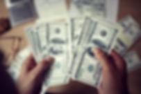 man-counting-money-with-calculator-PQ3NG