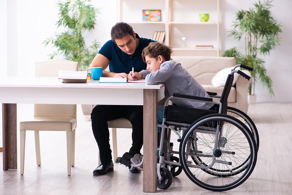Boy in wheelchair receiving tutoring