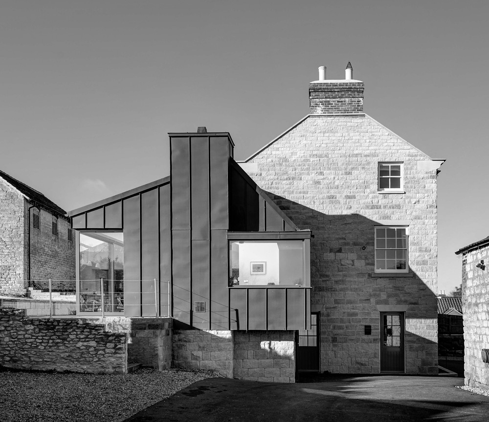 Contemporary standing seam extension to historic building in conservation area and National Park