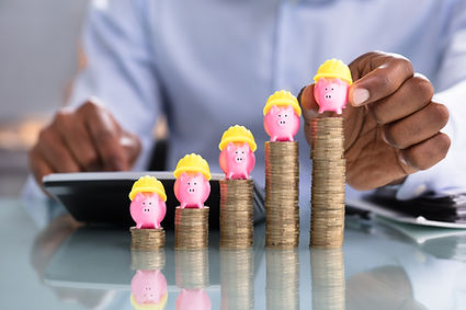 Close-up Of Business Person Placing Piggybank With Yellow Hardhat On Stacked Coins Over Re
