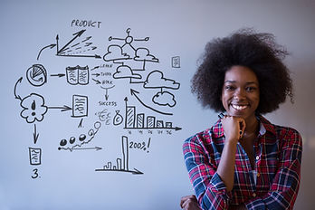 Young successful African American beautiful woman writes on a board meeting in a large mod