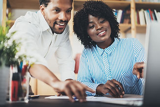 Two young coworkers working together in a modern office.Black business partners discussing