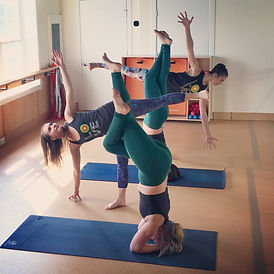 Melissa practicing yoga poses with friends in the studio.