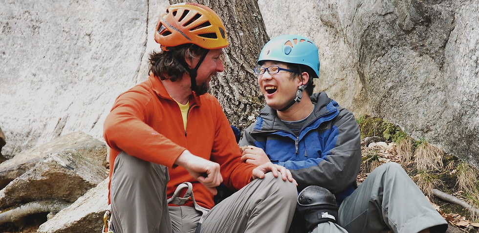 A volunteer laughs with a climber while taking a break.