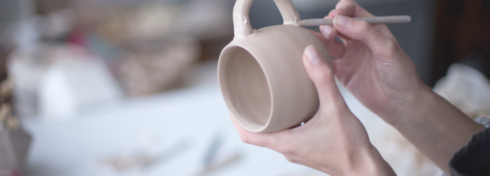 Female Potter Making Mug