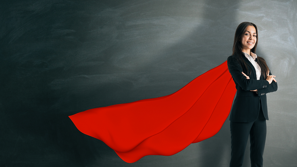A woman stands with a flowing red superhero cape.
