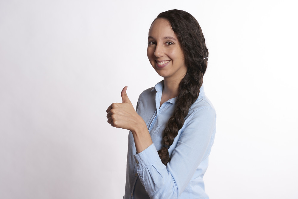 Smiling woman giving a thumbs up for good customer service