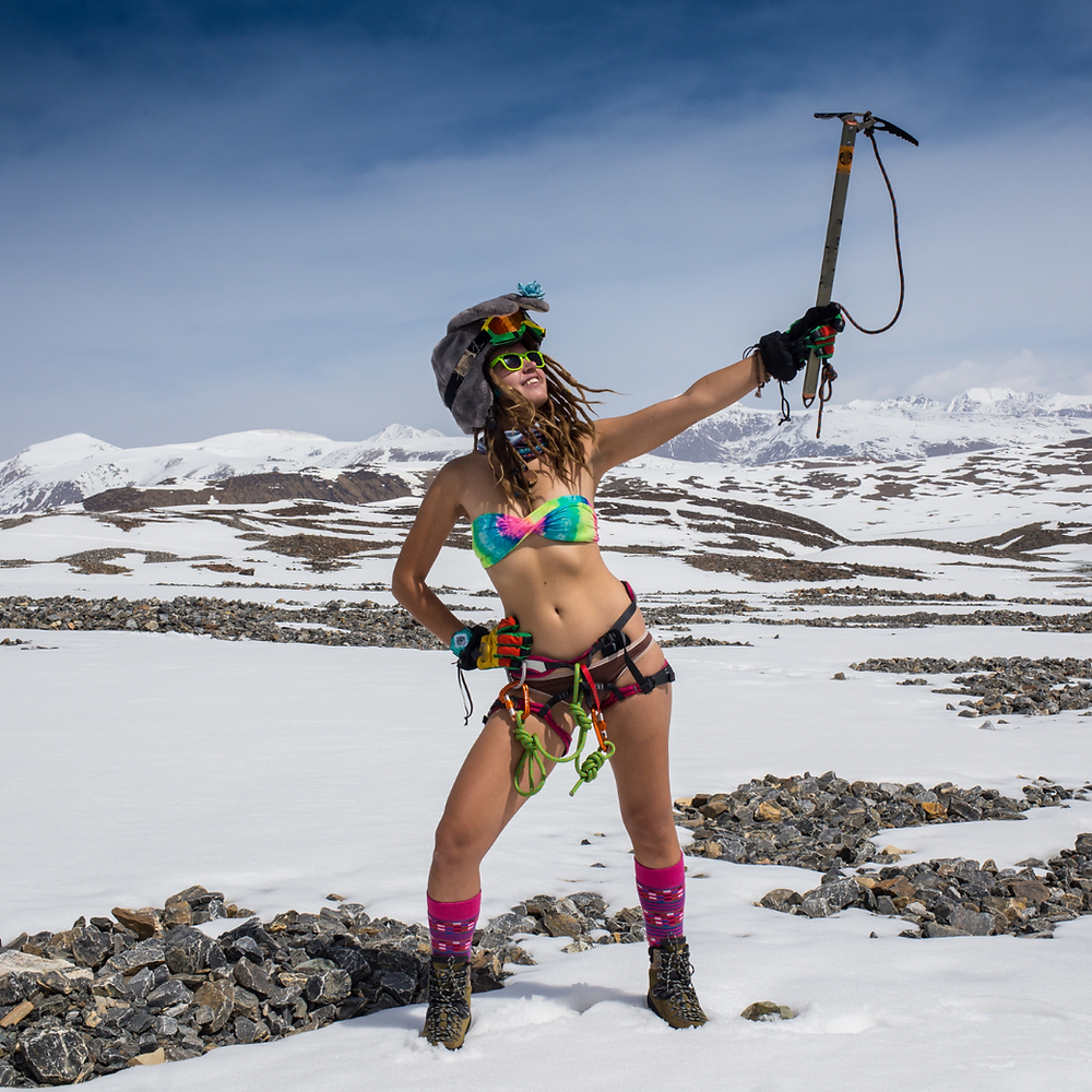 A scantily clad woman is at the summit of a mountain holding up a pick axe