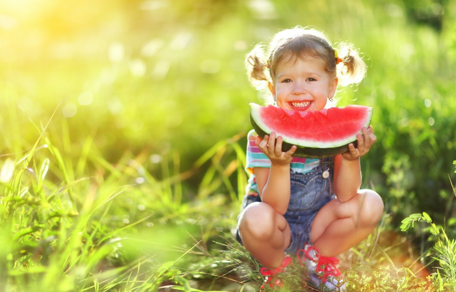 young girl eating slice of watermelon in a field