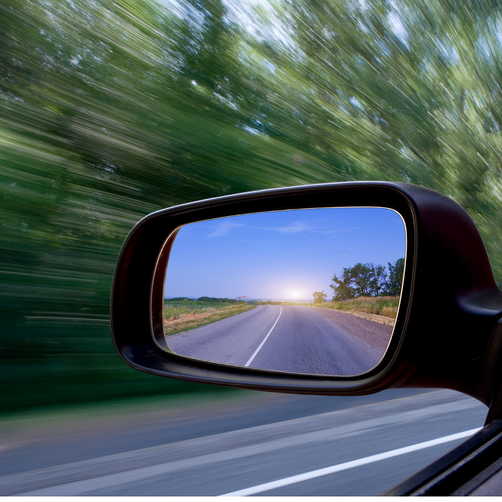 A rearview mirror shows the road behind