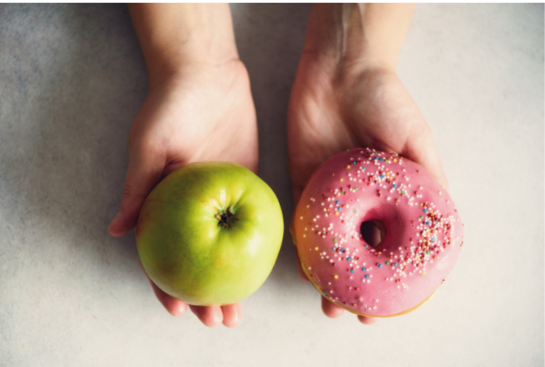 hands holding an apple and a donut