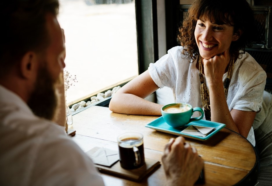 man and woman in coffee shop in conversation