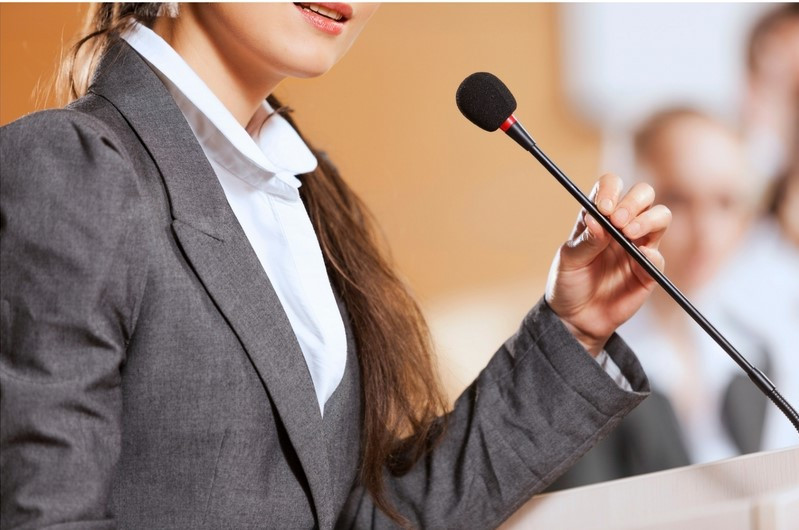 woman standing at a microphone giving a presentation