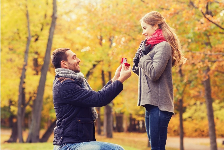 man on bended knee proposing to girlfriend in autumn woods