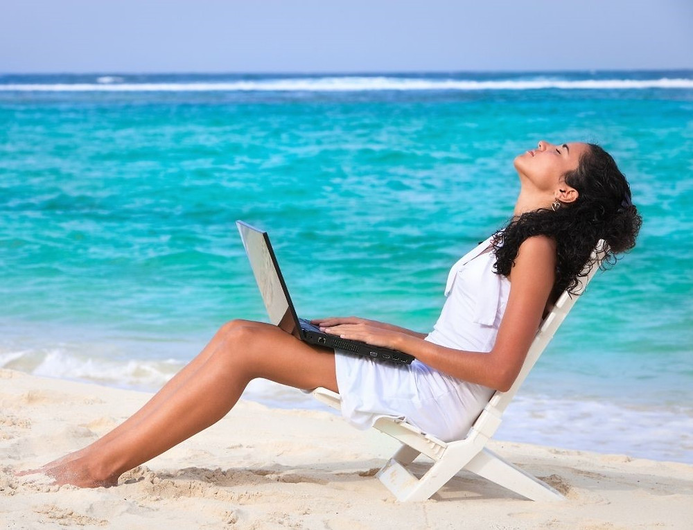 Woman sitting on the beach holding a laptop