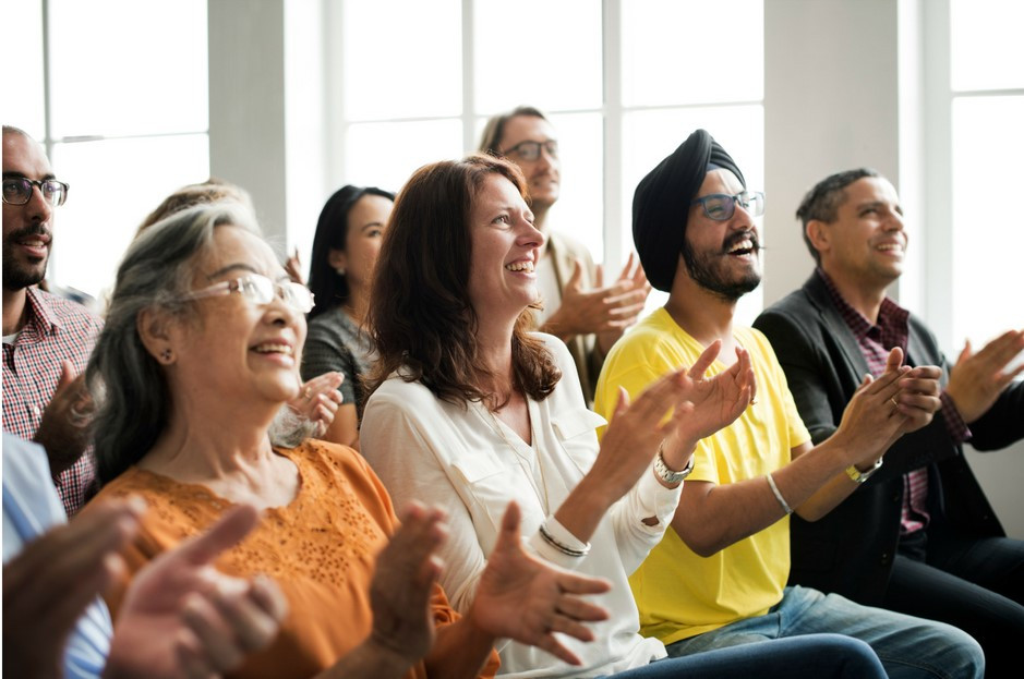 Multi cultural adult audience clapping with enthusiasm