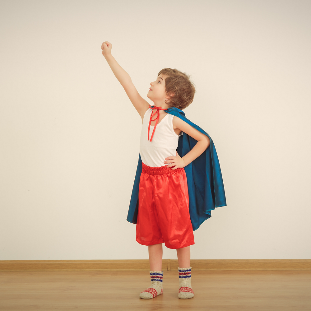 A young child in a superhero costume with fist raised in the air.