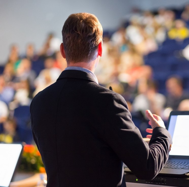 man standing at a podium commanding the audience
