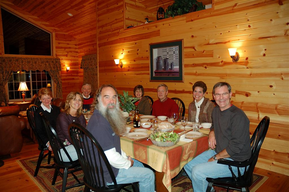 Group of adult friends around a dinner table in lodge in Michigan