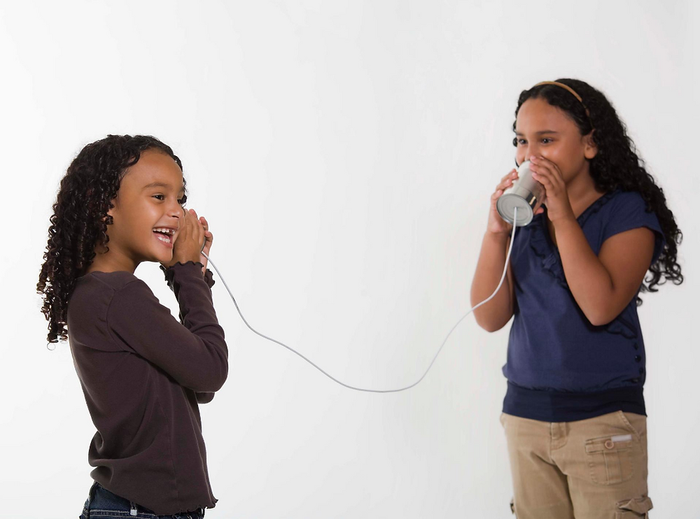 Two young girls play telephone through tin cans