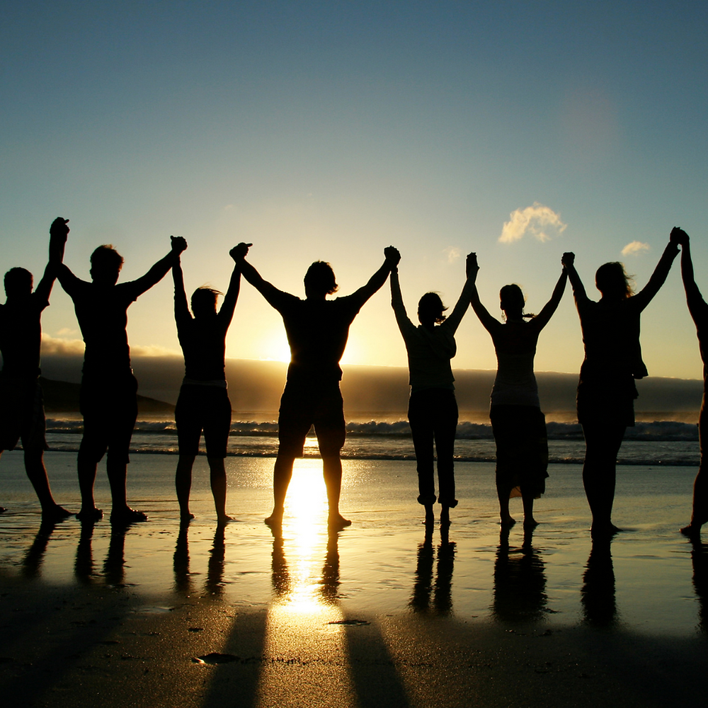 A group of people standing together on a beach holding hands upraised in the air.