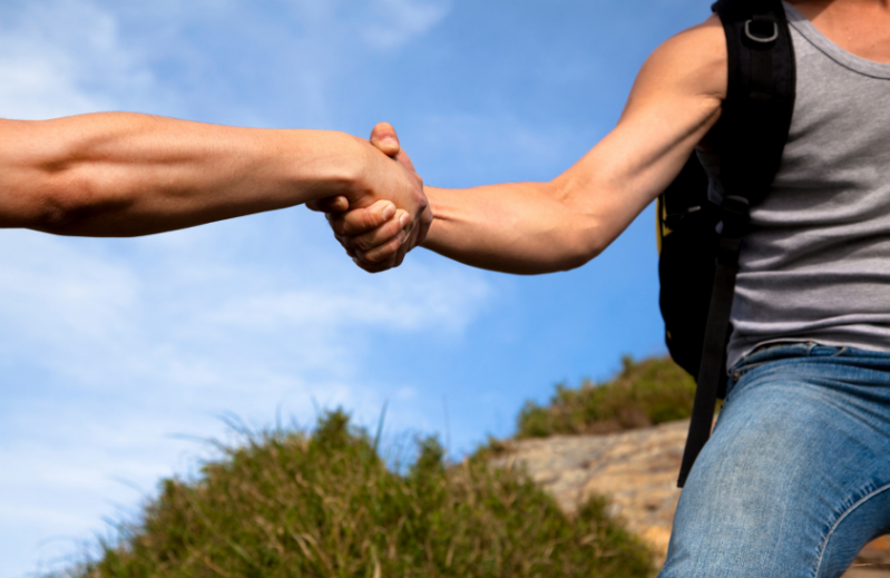 holding hands to give help to a hiker